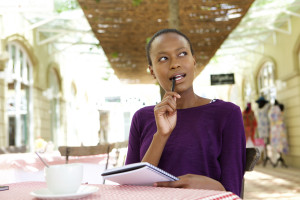 Portrait of young african woman sitting at cafe with notepad and looking away thinking