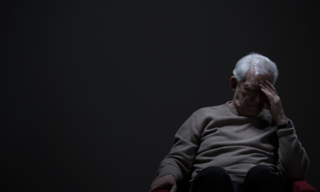 Despairing senior man on a dark background
